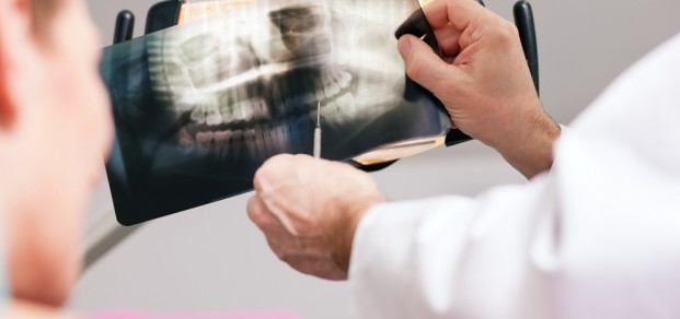 shutterstock_51359269 dentist and patient looking at x-ray