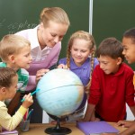 teacher looking at globe with children