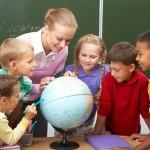teacher looking at globe with children