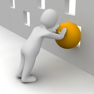 man pushing ball through square hole