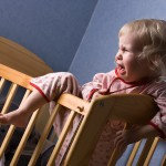 Crying young child in cot
