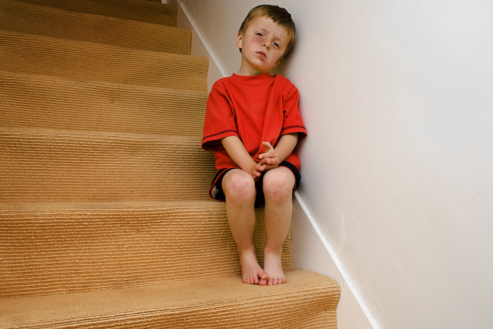 Child sitting on stairs looking sad
