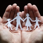 Hands holding paper cut-outs of people