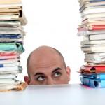 man staring at piles of paper