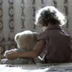 Young girl cuddling teddy bear