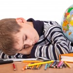 child sleeping on school books
