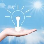 Hand holding a glowing lightbulb