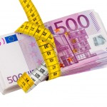 Measuring tape wrapped around a wad of Euros
