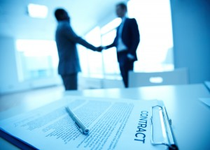 Two people shaking hands with a contract on the table