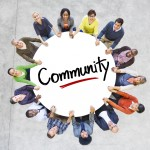 Group of people holding a circle with the word community on it