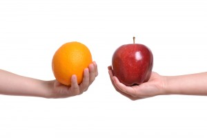 One hand holding an orange, the other holding an apple