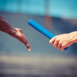 A baton being handed between athletes