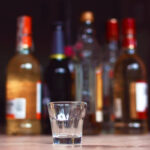 Empty,Small,Shots,Glass,In,Front,Of,Multiple,Blurry,Different