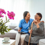 Health visitor and a senior woman during home visit. A nurse or a doctor examining a woman. Senior Woman Sitting In Chair  With Nurse In Retirement Home