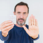 Senior,Man,Holding,Pharmaceutical,Pills,Over,Isolated,Background,With,Open