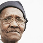 Closeup,Portrait,Of,Elderly,Woman,Wearing,Glasses,Over,White,Background