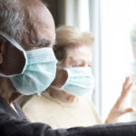 old man and woman with mask looking through window